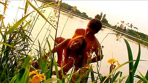 Пацан жарит свою подружку на закате около реки