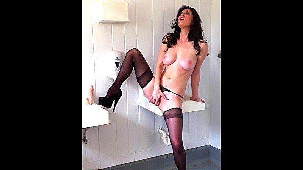 Сексуальная милфа раздевается и мастурбирует в общественном туалете