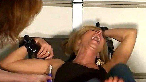 Щекотит зубной щёткой прикованную к креслу блондинку