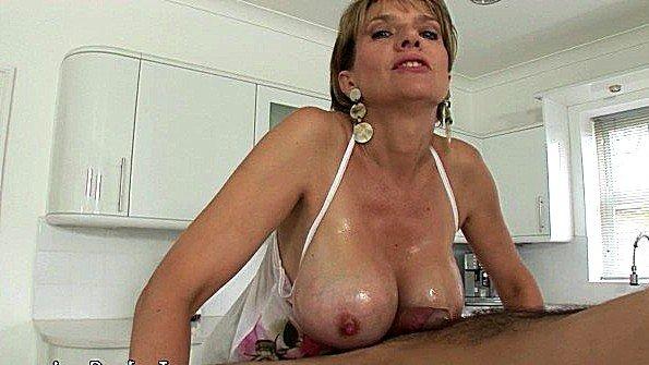 Большегрудая леди делает массаж члену своими титьками на кухне
